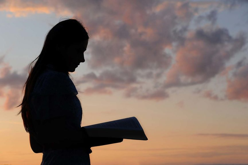 teenage girl with Bible at sunset