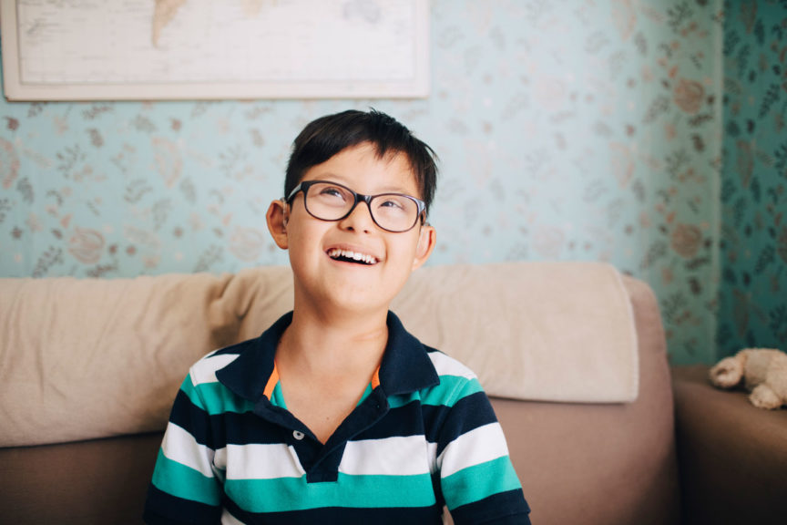 Thoughtful boy laughing while sitting on sofa at home