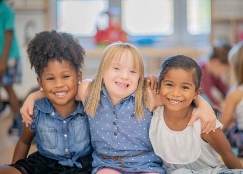 Three girls hugging friends at kindergarten