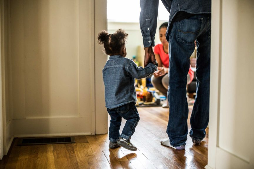toddler and dad walking towards mother