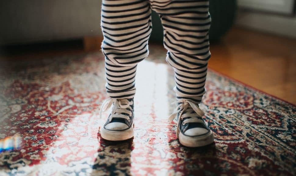 Toddler wearing sneakers standing on carpet