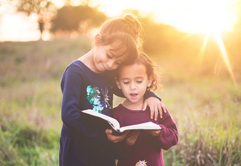 Girls reading outside with sunset