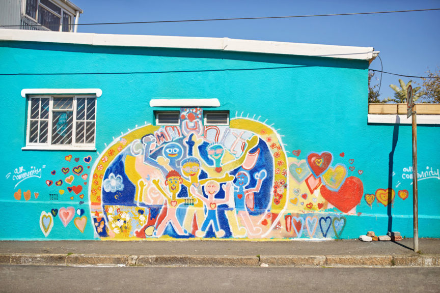 Vibrant community mural on sunny urban wall