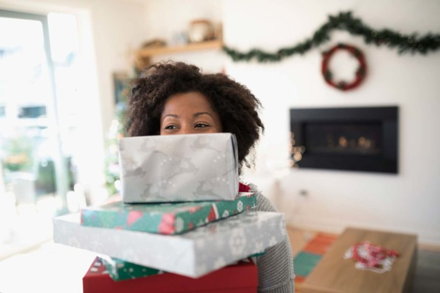 Portrait woman carrying stack of Christmas gifts