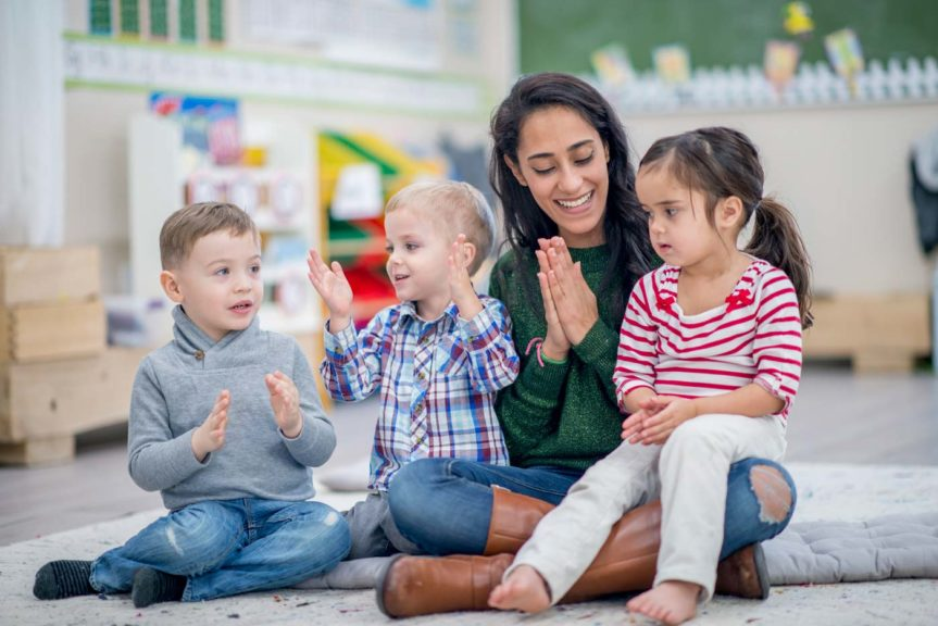 woman clapping to music with small children