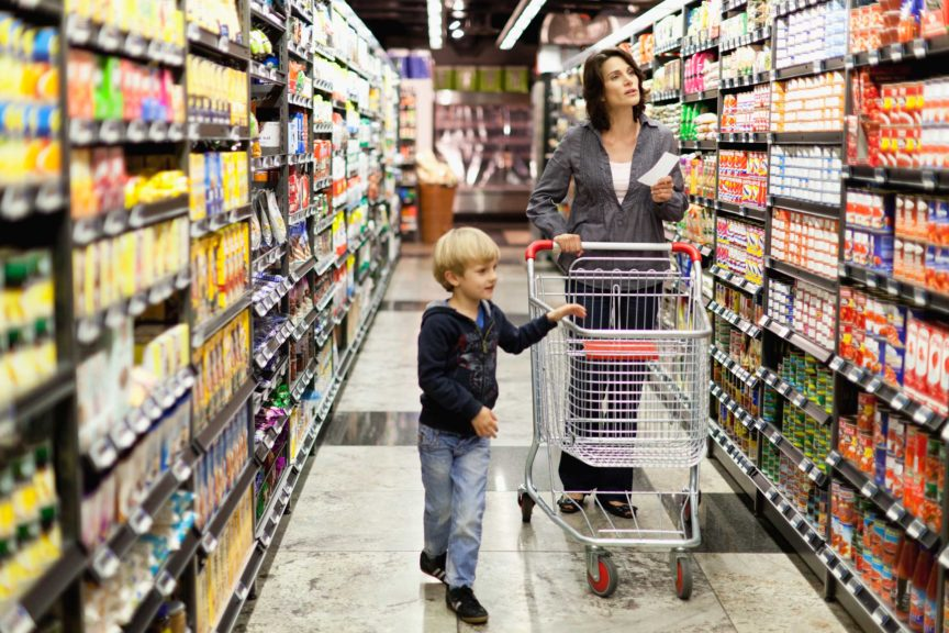 Woman grocery shopping with son