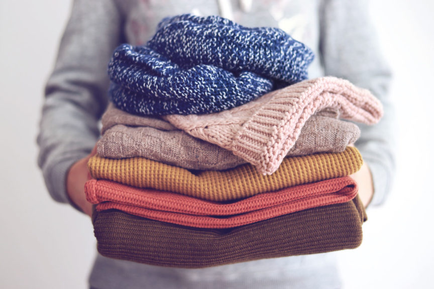 Woman holding fall color sweaters