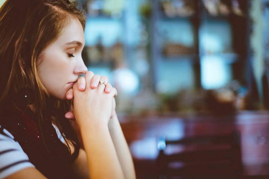 woman-praying-sitting-table