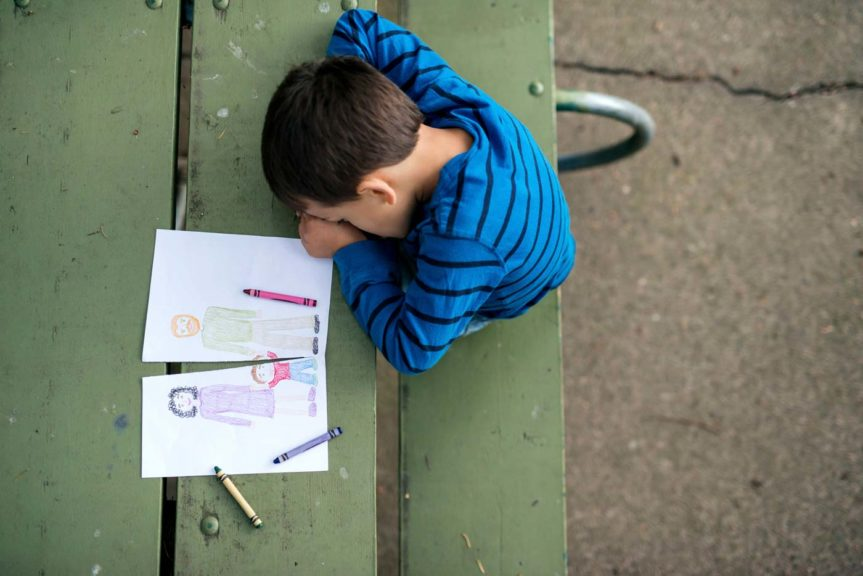 oung boy looking sad at drawing of a broken family