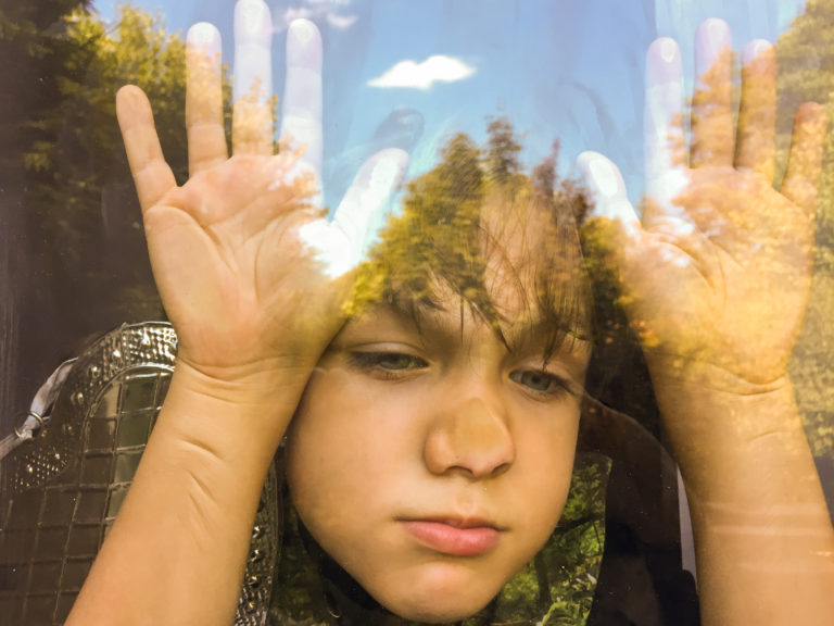 Young boy smashing face against window